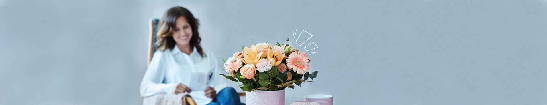 I förgrunden på ett soffbord står en vas med en vacker bukett i aprikos och orange, i fåtöljen i bakgrunden sitter en leende kvinna och läser en hälsning som följt med blombudet.