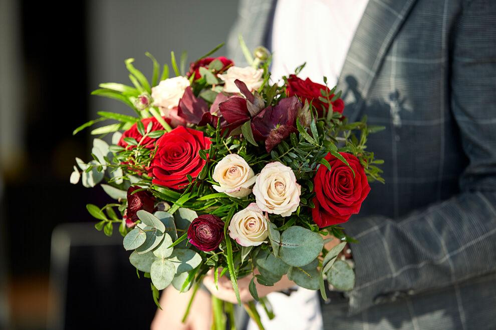 En man håller en bukett rosor.