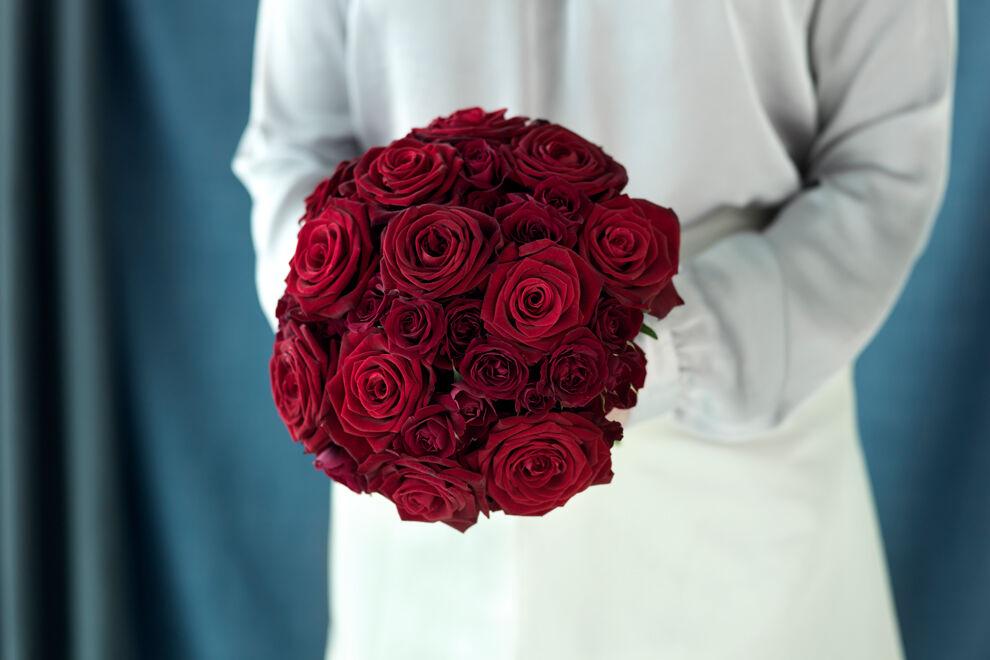 En kvinna i vit klänning håller en bukett röda rosor.