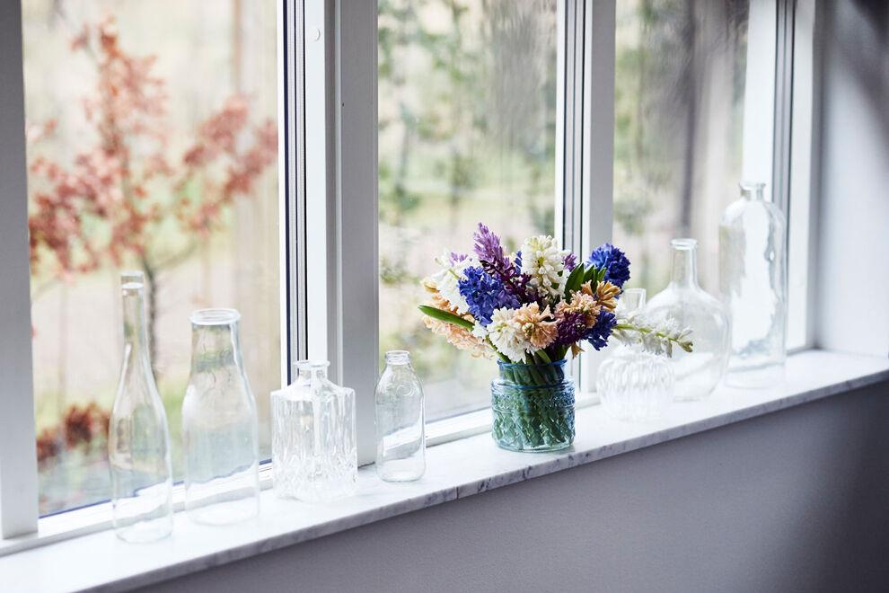 Ett vitt fönster med flera glasflaskor och glasvaser, i en av dem står en färgsprakande hyacintbukett i blått, laxfärgat, vitt och lila