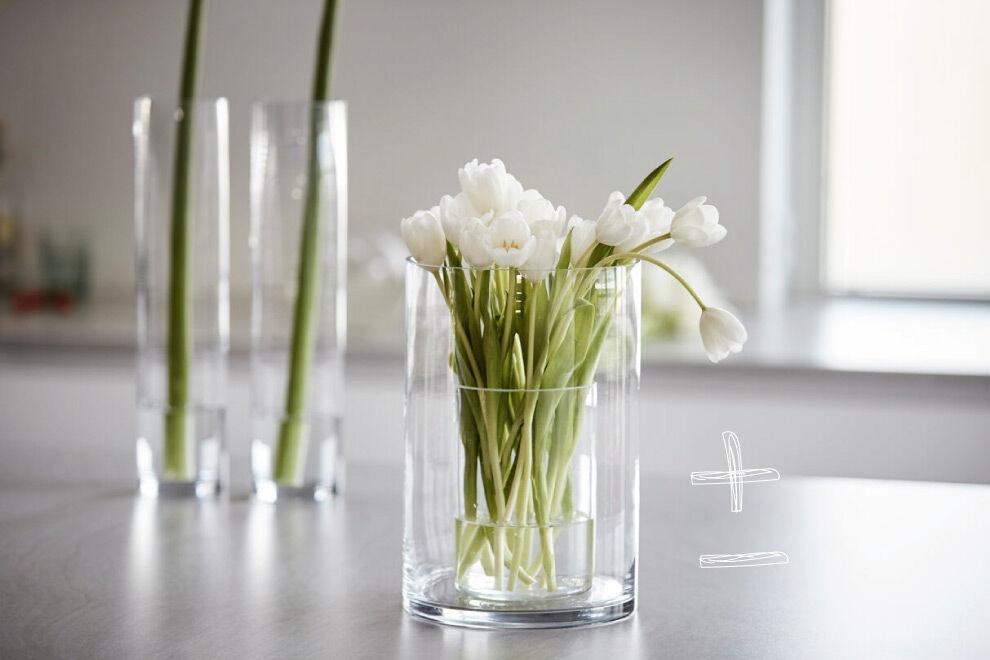 En bukett vita tulpaner på en bänk i ett kök.