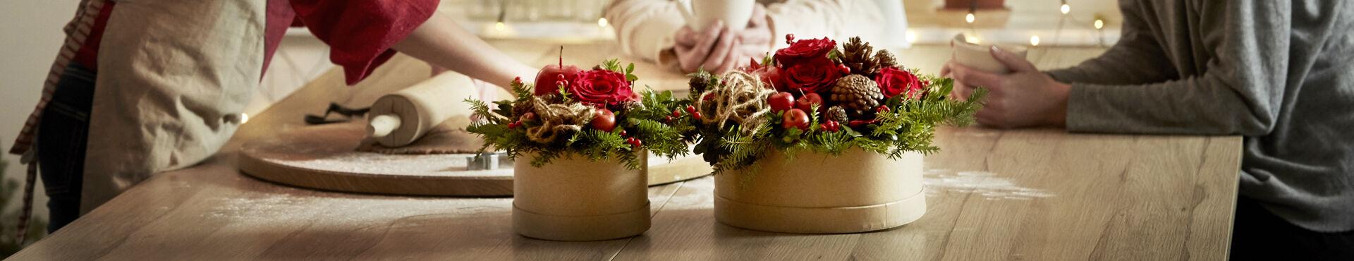 Två vackra julfina arrangemang i runda pappaskar står på en köksbänk, i bakrunden bakar några barn pepparkakor.